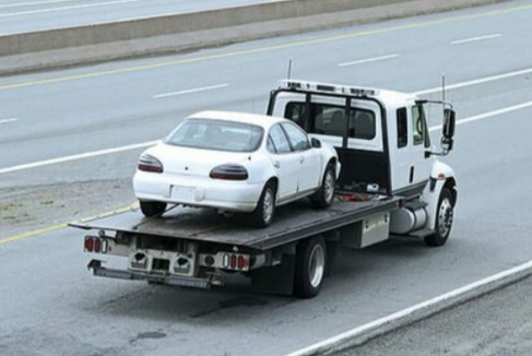 Picture of a white flatbed tow truck carrying a white car on its bed.